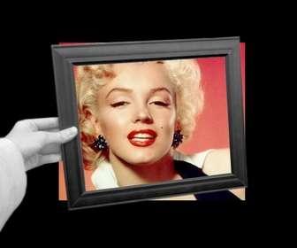 Ejemplo: Curioso fotomontaje en el que tu foto aparecerá como fondo en blanco y negro y dentro del marco de cuadro que sostiene una mano a color.