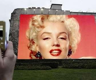 Ejemplo: Fotomontaje para que tu foto o la imagen de tu elección, aparezca en una gran valla publicitaria iluminada mientras, una mano saca una foto con el móvil.