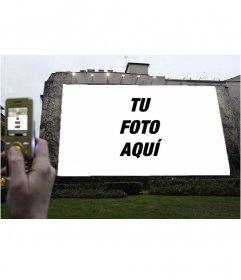 Fotomontaje para que tu foto o la imagen de tu elección, aparezca en una gran valla publicitaria iluminada mientras, una mano saca una foto con el móvil.
